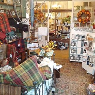Display room showing plaid cushions and throws, wreaths, assorted other gifts
