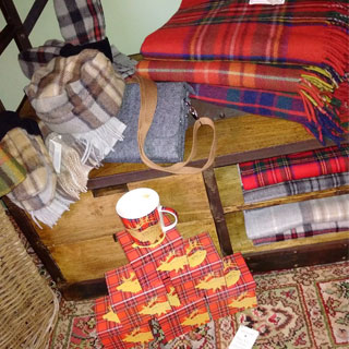 Red, plaid mugs with moose motif, tartan throws and blankets